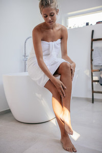 Beautiful young woman sitting on bathtub