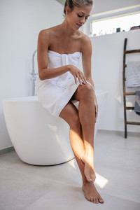 Sensual young woman sitting on bathtub
