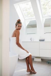 Beautiful woman sitting in bathroom