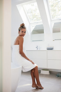 Beautiful woman sitting in bathroom