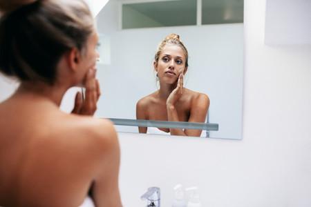 Beautiful woman applying moisturizer on face in bathroom