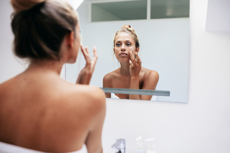 Woman in bathroom applying cream on face