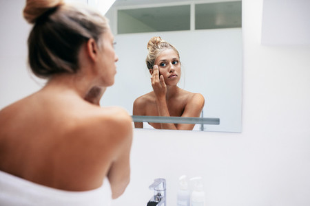 Woman applying cosmetic cream on face