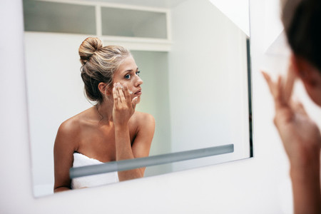 Reflection of a woman applying cosmetic cream