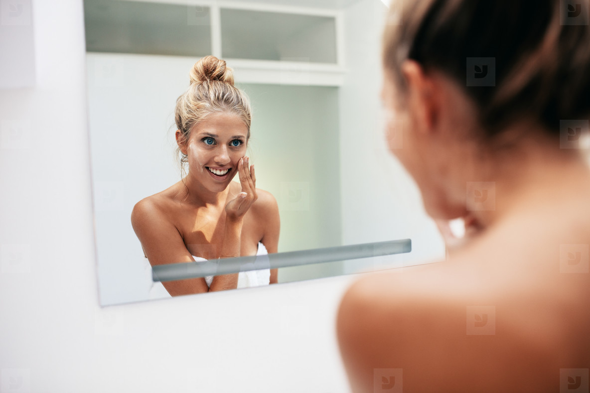 Smiling woman reflection applying face cream