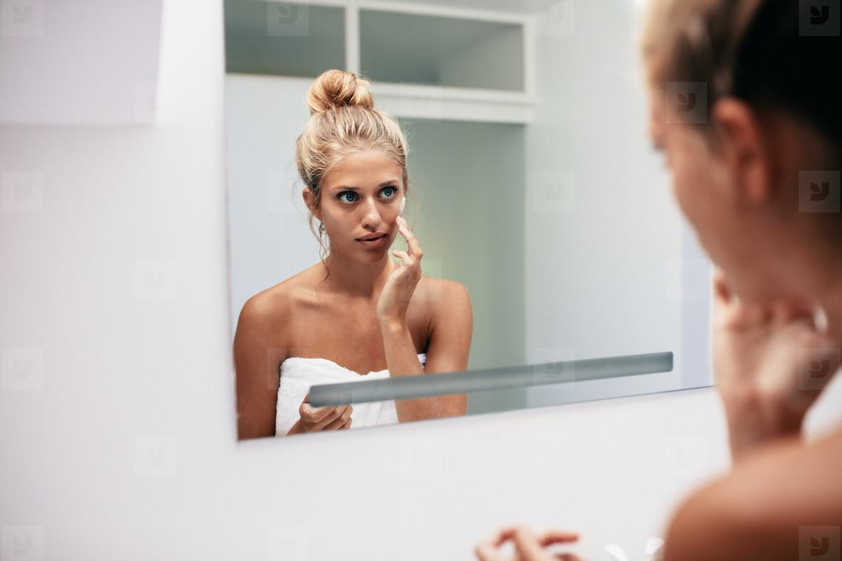 Beautiful young woman applying cosmetic cream