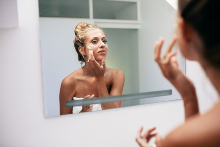 Young woman reflection in mirror applying cream
