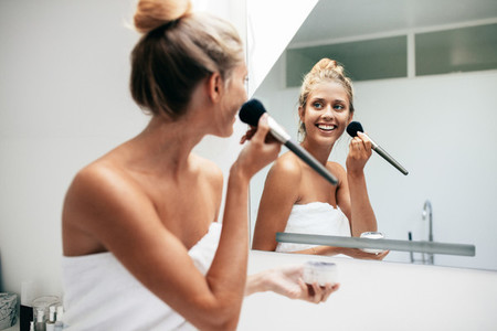 Beautiful young woman applying makeup in bathroom