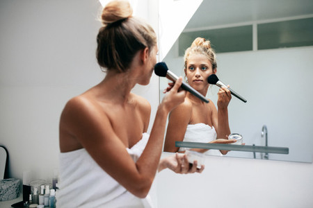 Beautiful female applying cosmetics on her face