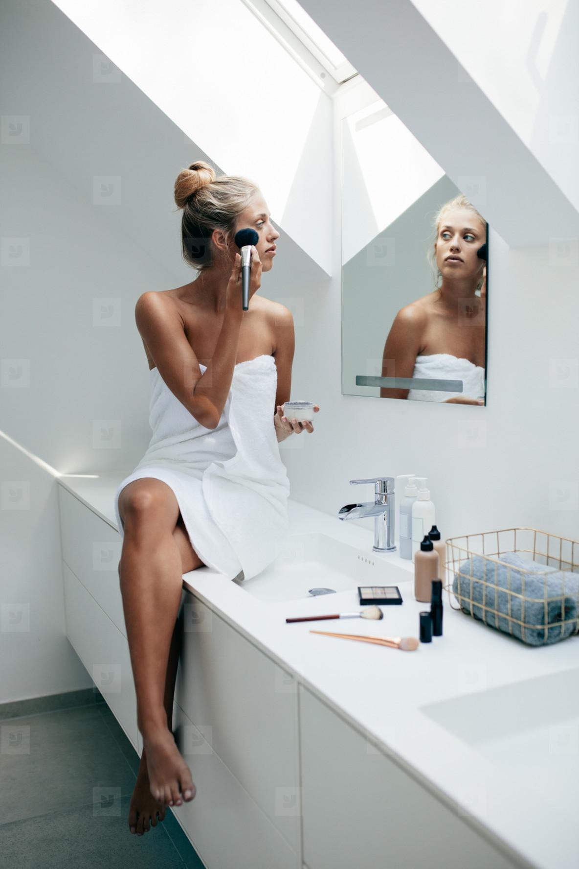Female putting on makeup in bathroom