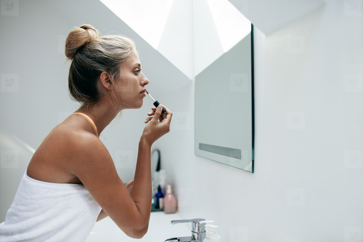 Woman applying lipstick in bathroom