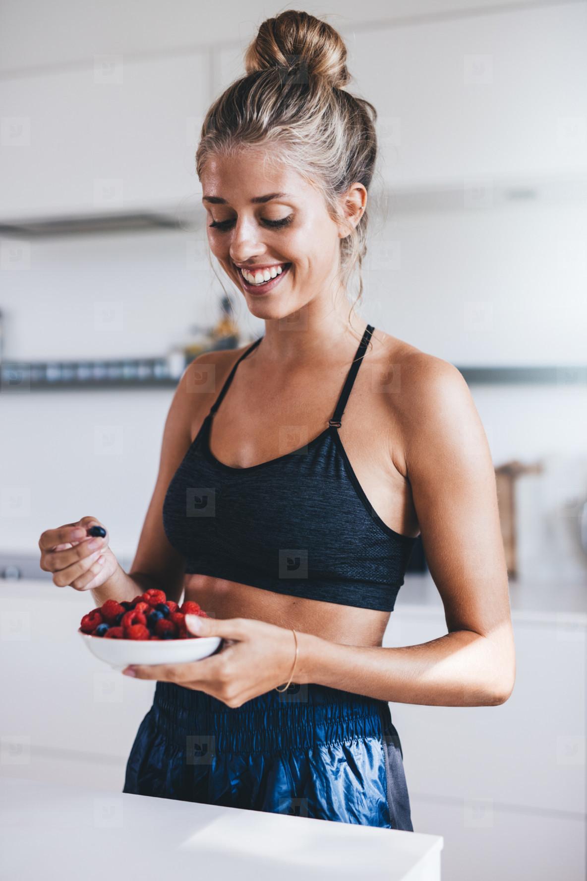 Happy female in kitchen eating fresh berries