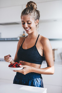 Happy female in kitchen eating fresh berries