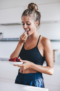 Beautiful young woman in kitchen eating berries