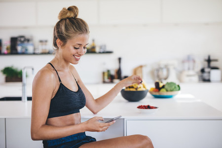 Smiling woman in kitchen using mobile phone