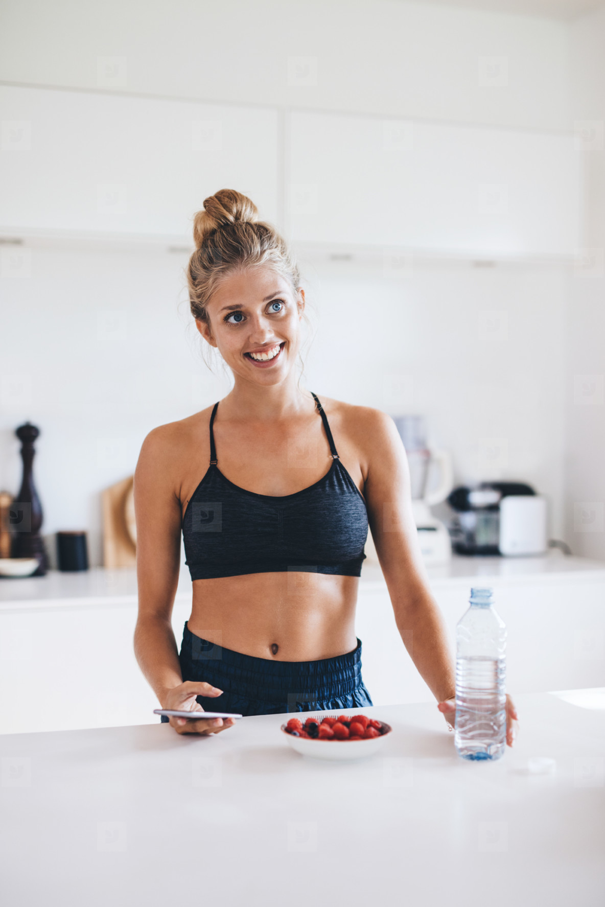 Young woman with berries in kitchen looking away smiling