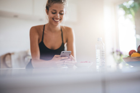 Smiling woman having breakfast and using cell phone in kitchen