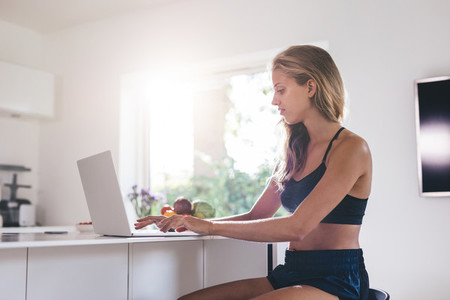 Beautiful woman sitting by kitchen counter and using laptop