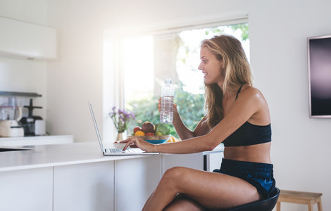 Beautiful woman using laptop computer in the kitchen