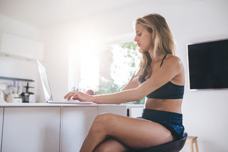 Young woman using laptop computer in the kitchen