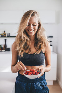 Smiling woman having healthy breakfast at home