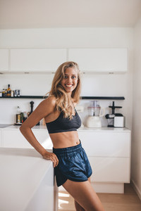 Female standing in kitchen looking happy