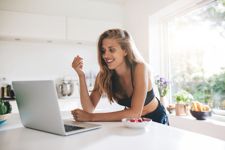 Beautiful young woman in kitchen with laptop