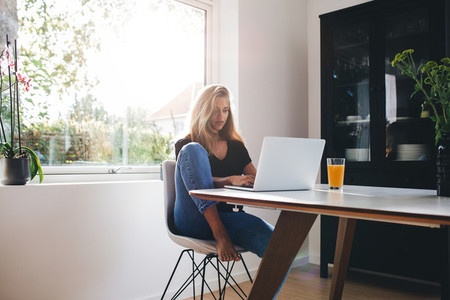 Young woman sitting in kitchen and working on laptop