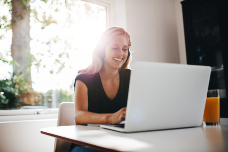 Happy female relaxing in kitchen with laptop