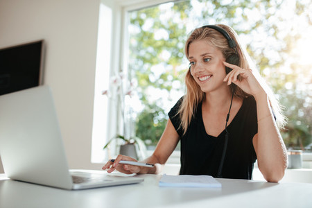 Smiling woman with headphones using laptop in kitchen