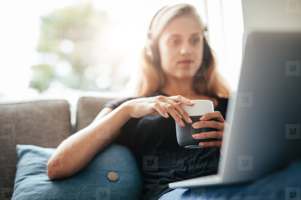 Female relaxing at home with cup of coffee and laptop
