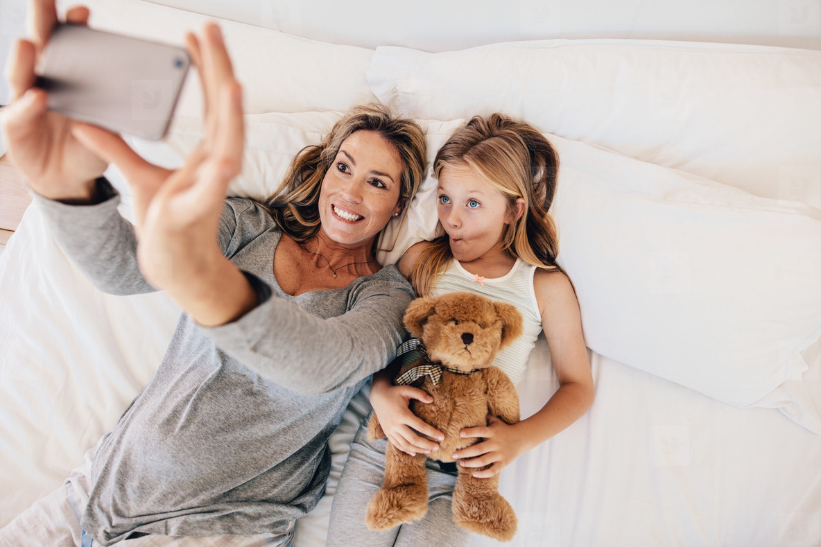 Mother and daughter lying on bed and taking selfie