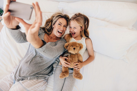 Young mother taking selfie with her daughter on bed