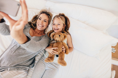 Young family taking selfie with smartphone in bed