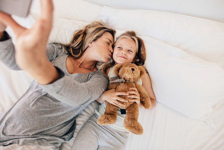 Mother and daughter taking selfie on bed