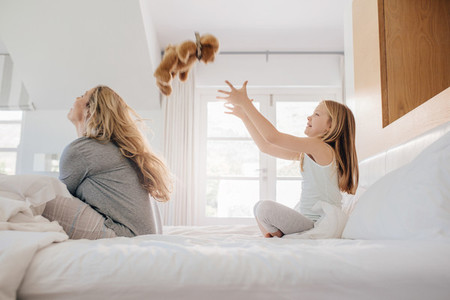 Mother and daughter playing with teddy bear on bed