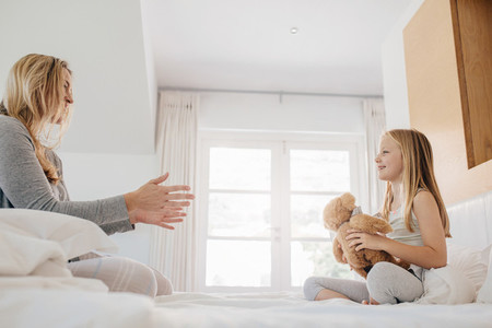 Little girl and woman playing with teddy bear