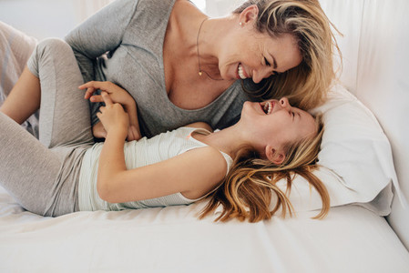Mother and daughter playing on bed and laughing