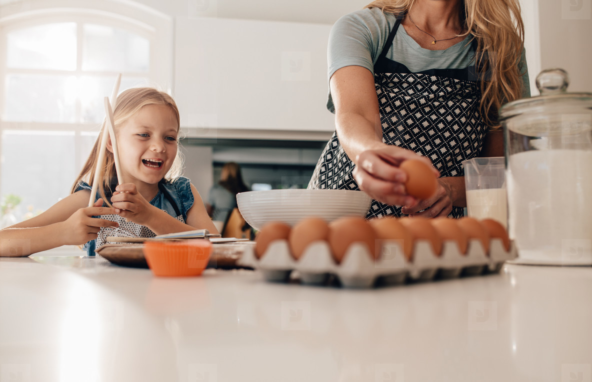 Little girl standing in kitchen with mother baking