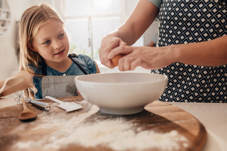 Mother and daughter preparing dough for baking