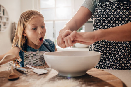 Excited young girl with mother preparing dough
