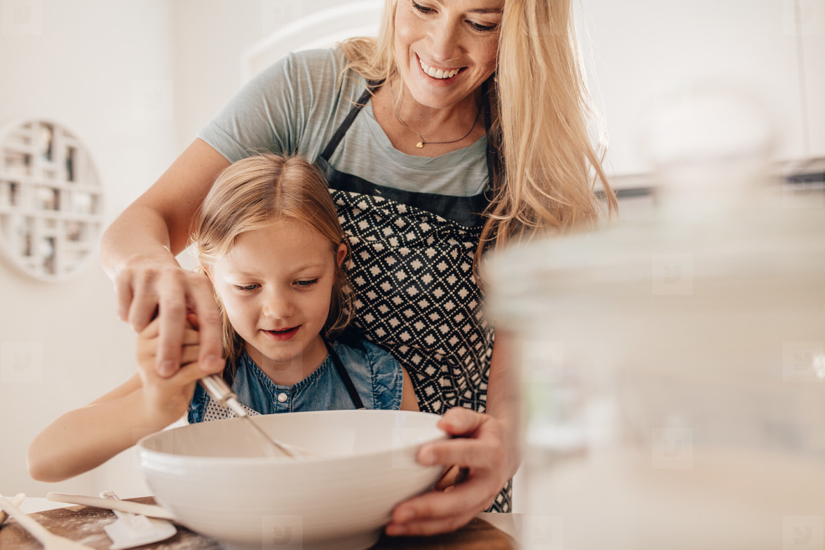 Mother and daughter kneading dough in kitchen