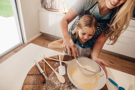 Woman with her daughter making batter in kitchen