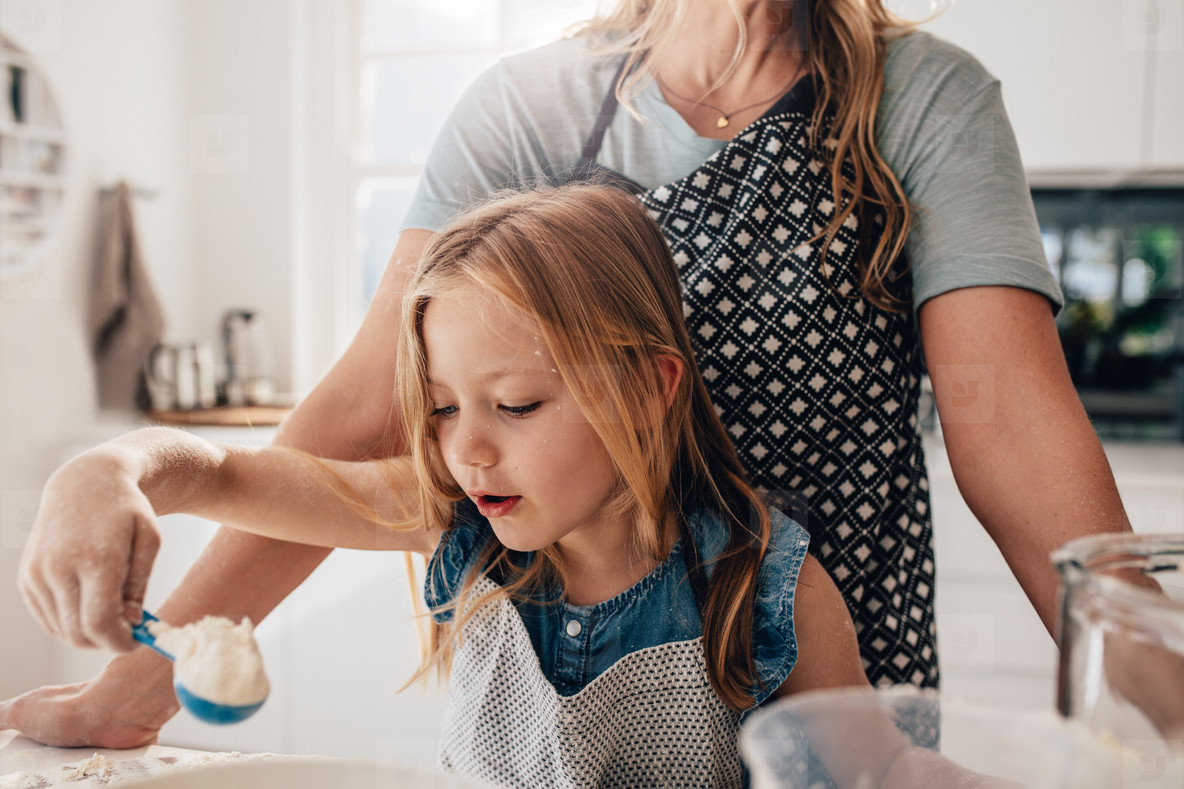 Little girl mixing batter in kitchen with her mother