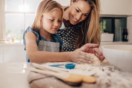 Mother teaching her daughter to make dough