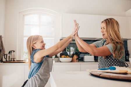 Little girl and her mother in kitchen giving high five