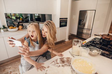 Mother taking selfie with her daughter in kitchen