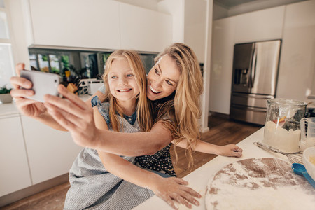 Happy young family of taking selfie in kitchen