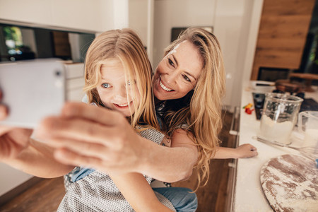 Beautiful woman and her cute daughter taking selfie in kitchen