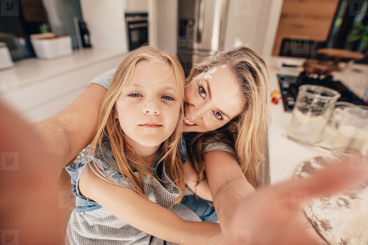 Happy woman and girl taking a selfie in kitchen